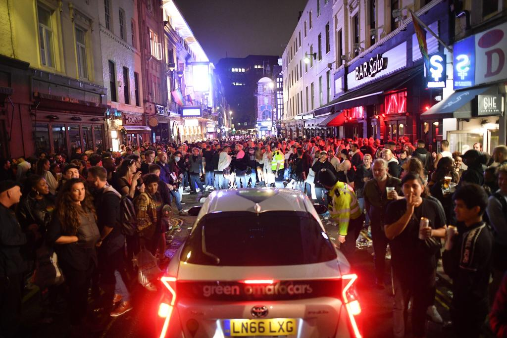 Police car passes through Soho street filled with revellers.
